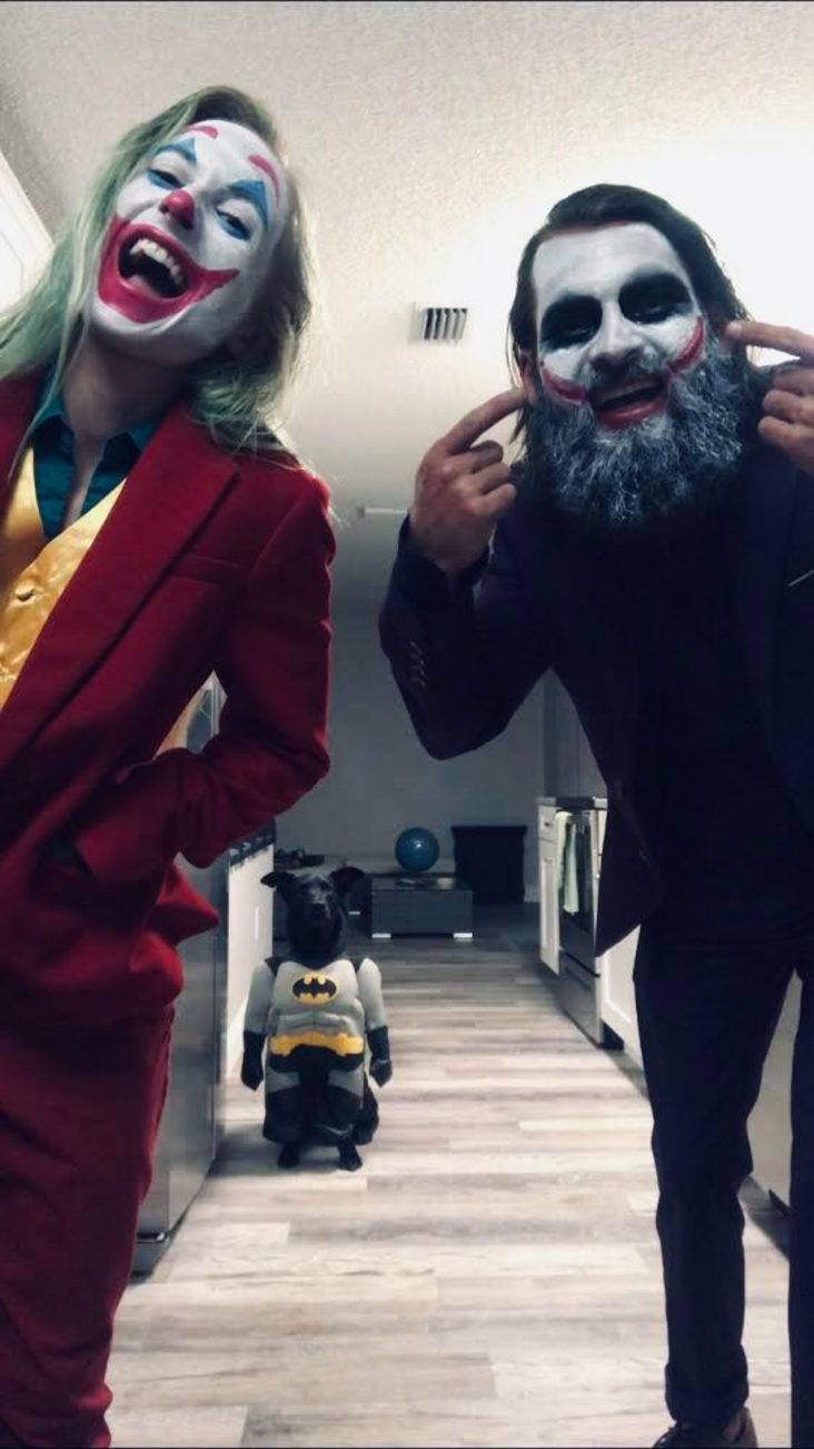 people dressed as the joker while the dog is in a batman costume.